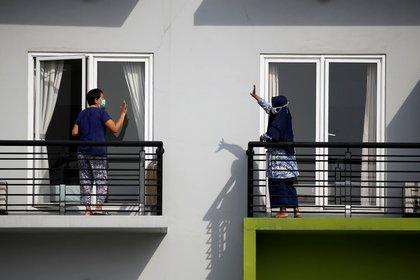 Pacientes se saludan desde sus balcones en un centro de capacitación, que se ha convertido en una casa de cuarentena, en Tangerang, en las afueras de Yakarta, Indonesia, en medio del brote de coronavirus  (Reuters)