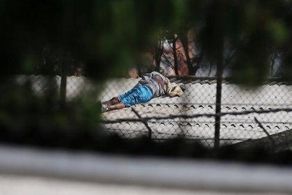 El cuerpo de un hombre se ve en el techo de un edificio dentro de la prisión La Modelo después de un motín de prisioneros que exigían medidas sanitarias del gobierno contra la propagación de la enfermedad coronavirus (COVID-19) en Bogotá, Colombia, el 22 de marzo de 2020