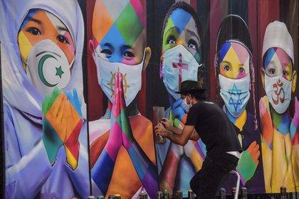 """El artista brasileño Eduardo Kobra termina su mural """"Coexistencia"""" que muestra a niños cubiertos con tapabocas con los símboles de diferentes religiones en Itu, a unos 100 kilómetros de San Pablo, Brasil"""