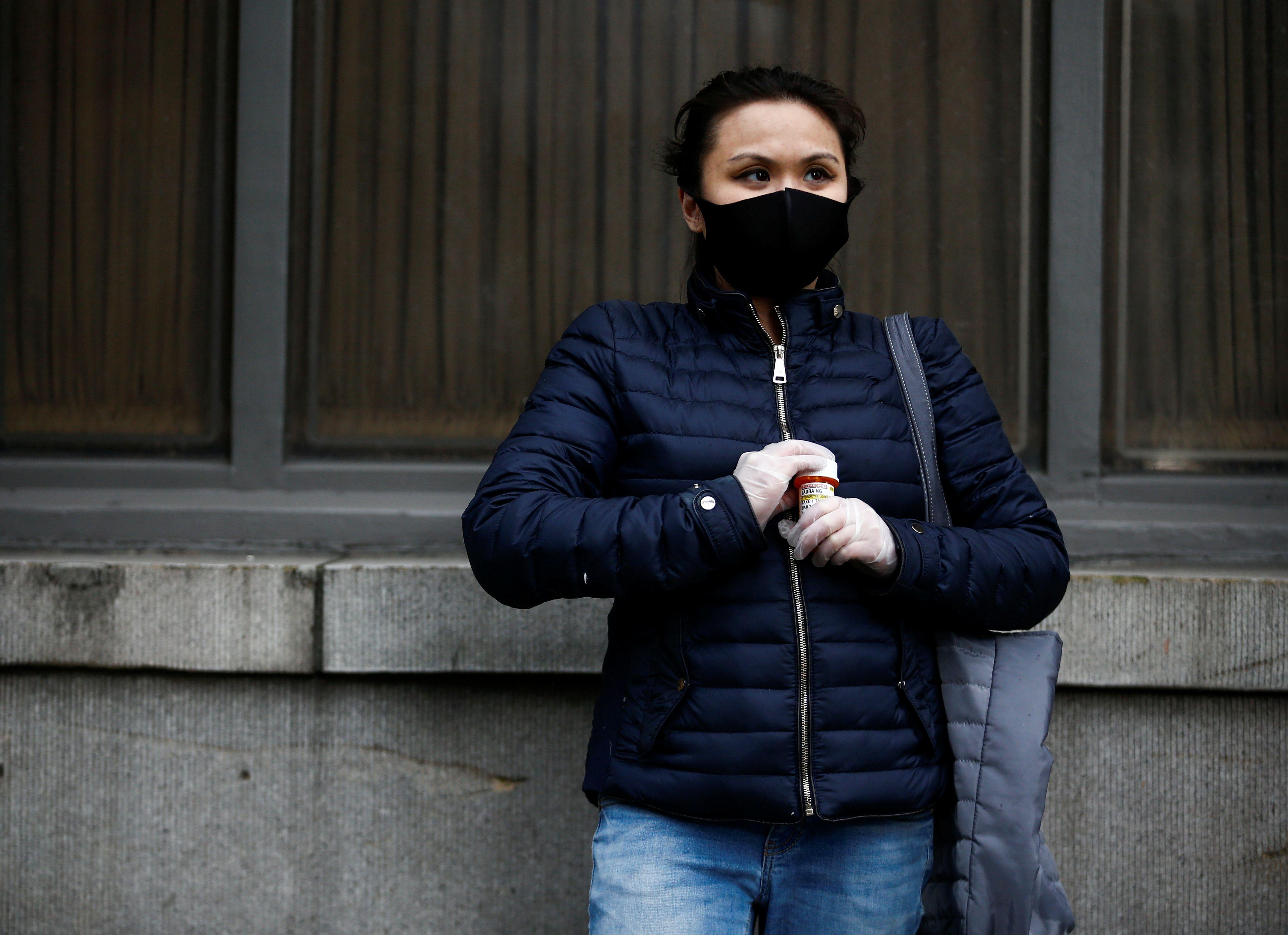 Una mujer se toma un medicamento mientras usa una mascarilla para protegerse del coronavirus