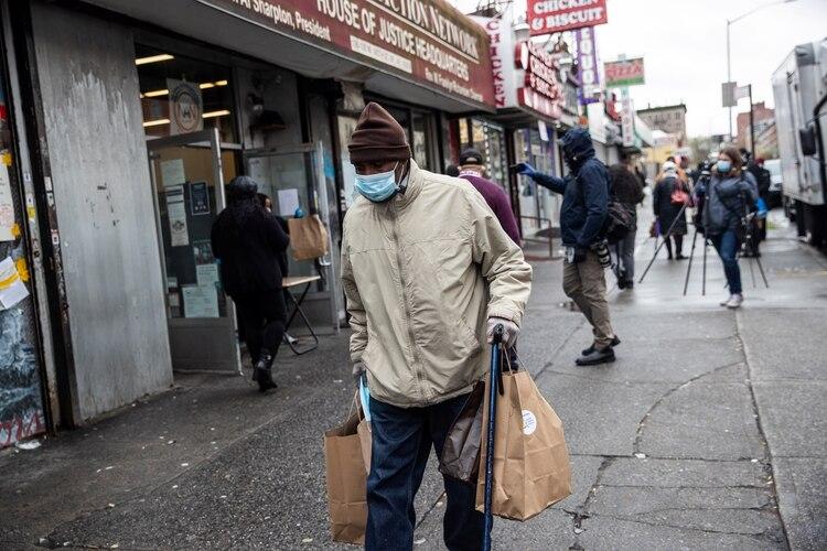 Un hombre con una máscara protectora tras recibir comidas gratis durante el brote de coronavirus en la ciudad de Nueva York, EE.UU., el 18 de abril de 2020. (REUTERS/Jeenah Moon)
