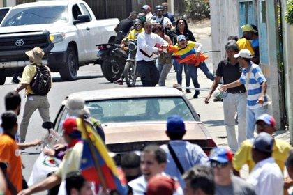 Un simpatizante del dictador de Venezuela, Nicolás Maduro, agrede a una mujer opositora, durante una manifestación en Barquisimeto,