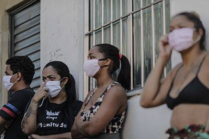 Un grupo de residentes de la favela de Mandela, en la zona norte de Río de Janeiro), a la espera de alimentos y ayudas, durante la actual pandemia por el COVID-19. EFE/Antonio Lacerda
