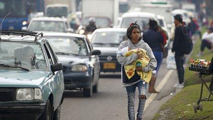 Una migrante venezolana, acunando a un bebé, camina por una avenida donde pide a los conductores su cambio de repuesto, en Bogotá, Colombia. (Foto AP/Fernando Vergara)