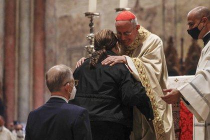 Los padres de Carlo Acutis son abrazados por el Cardenal, Agostino Vallini, durante la beatificación de su hijo en Asís  (AP Photo/Gregorio Borgia)