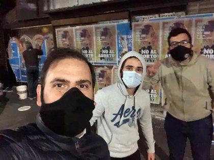 Militantes pegando los afiches en la noche del jueves