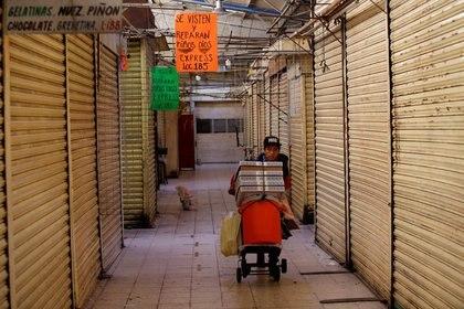 FOTO DE ARCHIVO: Un hombre empuja un carrito mientras pasa por negocios cerrados en un mercado, en medio de la propagación de la enfermedad por coronavirus (COVID-19), en la Ciudad de México, México, 22 de abril de 2020. REUTERS / Gustavo Graf