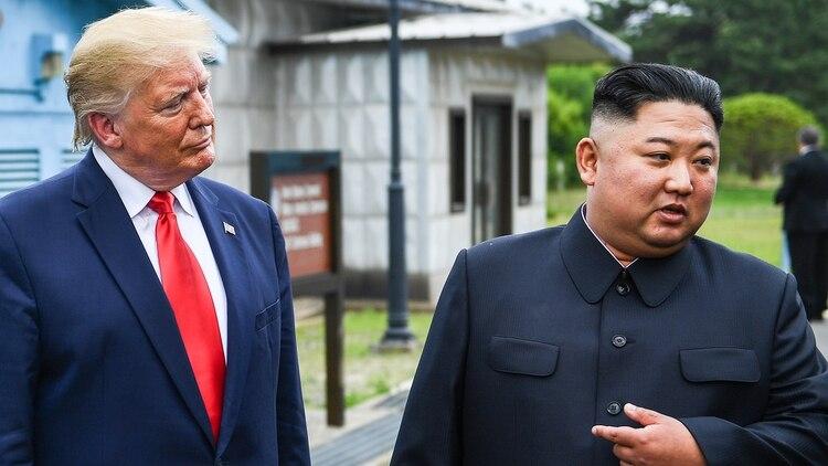 Trump y Kim Jong-un en la zona desmilitarziada que separa las dos Coreas en junio de 2019 (AFP)