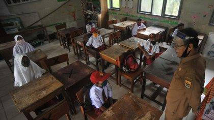 Estudiantes y maestros usan máscaras, después de que el gobierno indonesio reabriera las escuelas en medio del brote de coronavirus, en Pariaman, en la provincia de Sumatra Occidental, Indonesia, el 13 de julio de 2020 (Antara Foto/Iggoy el Fitra/via Reuters)