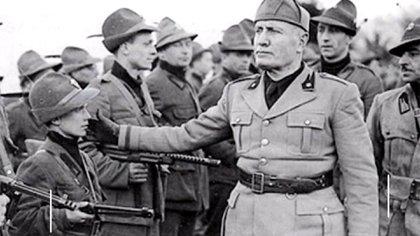 Benito Mussolini en un desfile de camisas negras, con veteranos y niños entre sus filas