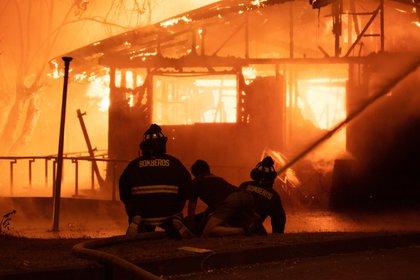 Bomberos trabajan en apagar las llamas de la comisaría, atacada tras la muerte de un malabarista callejero en Panguipulli, Chile. REUTERS/Andres Quezada NO RESALES. NO ARCHIVES