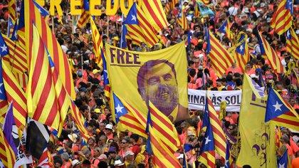 Manifestantes sostienen un estandarte que exige libertad para el dirigente encarcelado catalán Oriol Junqueras mientras se reúnen para participar en una manifestación independentista en Barcelon (LLUIS GENE / AFP)