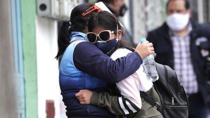 Dos personas aguardan saber el estado de salud de un ser querido en Quito (AP Photo/Dolores Ochoa)