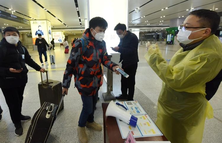 Un viajero muestra un código QR verde en su teléfono móvil que indica su estado de salud a un trabajador en una estación de ferrocarril en Hangzhou, provincia de Zhejiang, China, 17 de febrero de 2020. (China Daily vía Reuters)