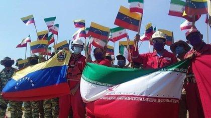 Trabajadores con banderas de Irán y Venezuela durante el arribo de un barco de transporte de combustible iraní al puerto de Cardón, Venezuela