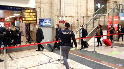 Agentes del orden controlan a los pasajeros en la estación central de trenes de Milán, Italia, el 2 de abril de 2021. Italia está pasando la Semana Santa encerrada después de que el gobierno convirtió a toda la nación en una 'zona roja' COVID-19 desde el 3 de abril hasta el lunes de Pascua. EFE / EPA / Paolo Salmoirago