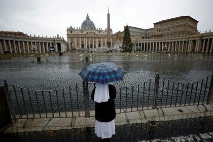 Imagen de archivo de una monja mirando una vacía Plaza de San Pedro el día de Año Nuevo en medio de la pandemia de COVID-19 en El Vaticano. 1 de enero, 2021 (REUTERS/Guglielmo Mangiapane/Archivo)