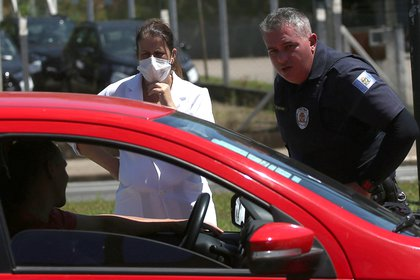 Una trabajadora de la salud y un oficial de policía hablan con un conductor en una barrera sanitaria en San Pablo, Brasil (REUTRES/Rahel Patrasso)