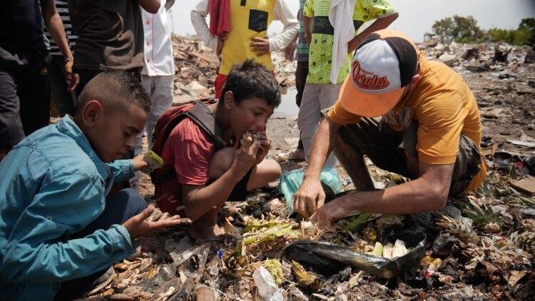 Juan junto a otros niños comiendo de la basura. (Gentileza Sky News)