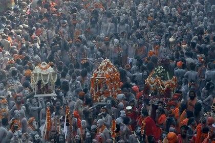 Devotos peregrinan hasta llegar a las orillas del río Ganges para sumergirse y bendecir a sus familias.