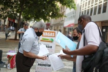 """Hombres entregan currículums cerca de una lista de trabajos en una pizarra que dice """"Vacantes"""" en el centro de San Pablo, Brasil, el 6 de octubre de 2020 (REUTERS/Amanda Perobelli)"""