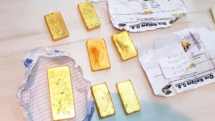 En esta foto, proporcionada por la Policía Federal de Brasil, se muestran barras de oro incautadas y efectivo después de una redada en una operación que presuntamente contrabandeó oro ilegal venezolano por decenas de millones de dólares, en Roraima, Brasil, el viernes 6 de diciembre de 2019 (Policía Federal de Brasil vía AP)