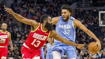 Jan 24, 2020; Minneapolis, Minnesota, USA; Minnesota Timberwolves center Karl-Anthony Towns (32) dribbles the ball behind his back as Houston Rockets guard James Harden (13) defends in the second half at Target Center. Mandatory Credit: Jesse Johnson-USA TODAY Sports