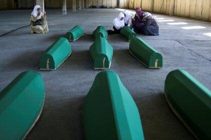 Mujeres musulmanas bosnias lloran cerca de los ataúdes que serán enterrados este sábado en el cementerio conmemorativo de Potocari, cerca de Srebrenica, Bosnia y Herzegovina, el 10 de julio de 2020 (REUTERS/Dado Ruvic)