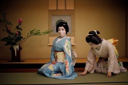 Mayu ajusta el kimono de Koiku, quienes son geishas, ya que Koiku usa una máscara protectora para posar para una fotografía, antes de trabajar en una fiesta organizada por clientes, donde se entretendrán con otras geishas, en Asada, un lujoso restaurante japonés, durante el brote de coronavirus (COVID-19), en Tokio, Japón. 23 de junio de 2020. REUTERS/Kim Kyung-hoon