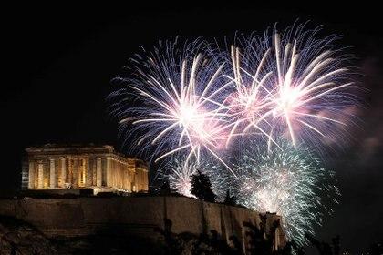 Fuegos artificiales explotan sobre el antiguo templo del Partenón en la cima de la colina de la Acrópolis durante las celebraciones del día de Año Nuevo en Atenas, Grecia (REUTERS/Costas Baltas)
