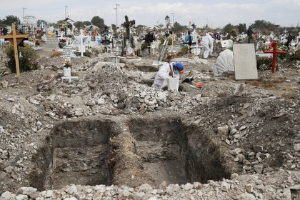 A cemetery worker wearing a protective suit digs new graves at the San Isidro Municipal cemetery, as the outbreak of the coronavirus disease (COVID-19) continues, in Ecatepec de Morelos, on the outskirts of Mexico City, Mexico February 11, 2021. REUTERS/Henry Romero