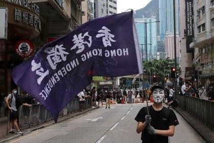 Un manifestante antigubernamental enmascarado sostiene una bandera en apoyo a la independencia de Hong Kong durante una marcha contra los planes de Pekín de imponer una ley de seguridad nacional en Hong Kong, China, el 24 de mayo de 2020. REUTERS/Tyrone Siu