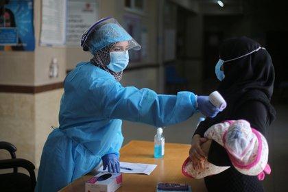 Una trabajadora del sistema de salud palestino le toma la temperatura a un bebé recién nacido  (REUTERS/Ibraheem Abu Mustafa)