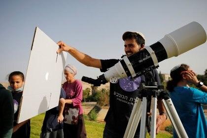 Un hombre usa un telescopio para proyectar el fenómeno