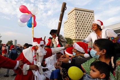 Un hombre vestido con el traje de Papá Noel distribuye dulces entre la gente durante una manifestación por la paz en Karachi, Pakistán (REUTERS/Akhtar Soomro)