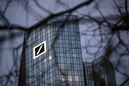 """A logo sits on the Deutsche Bank AG headquarters at dawn in Frankfurt, Germany, on Tuesday, Dec. 10, 2019. Deutsche Bank said revenue from fixed-income trading is up this quarter while warning that its mid-term profitability goal is now """"more ambitious"""" given the outlook for interest rates. Photographer: Alex Kraus/Bloomberg"""