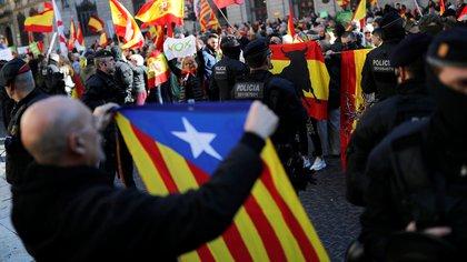 Un independentista catalán ondea la estelada (la bandera autonómica de Cataluña) frente a un grupo de manifestantes de derecha en favor de la unidad española