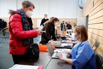 Trabajadores de la salud registrándose para recibir la vacuna COVID-19 de Pfizer-BioNTech en un centro de vacunación dentro de un gimnasio en Taverny cerca de París, Francia, el 9 de enero de 2021 (REUTERS/Benoit Tessier)