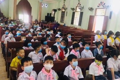 Decenas de chicos con barbijos participan de una misa en Vinh Phuc, Vietnam el 23 de febrero - REUTERS/Stringer