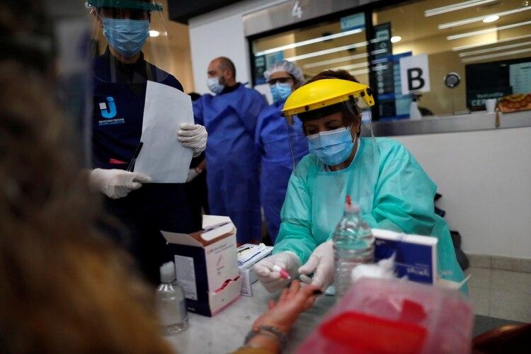 Un enfermero toma una muestra de sangre para análisis por COVID-19 en la estación Constitución - REUTERS/Agustin Marcarian