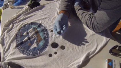 Un miembro de Blue Water Ventures inspecciona las monedas recuperadas del fondo del mar, frente a las costas de Carolina del Sur