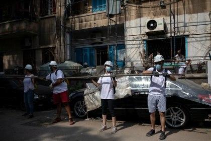 Los voluntarios cargan andamios para colocarlos alrededor de un edificio que fue dañado por la explosión en el puerto de Beirut, en el barrio de Karantina, Beirut, Líbano, el 13 de agosto de 2020.