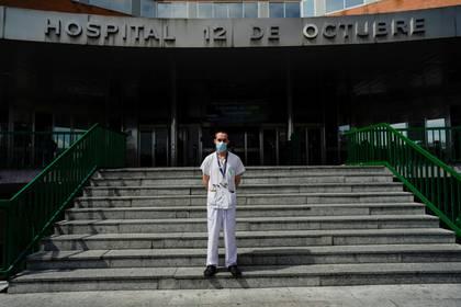 Christian Vigil, médico de cuidados intensivos, posa en la entrada principal del hospital 12 de Octubre en Madrid, España, el 8 de abril de 2020. (REUTERS/Juan Medina)