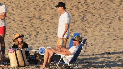 Matías Martin, Natalia Graciano y un amigo de ambos, en la playa al atardecer. Ellos con cap y ella con sombrero australiano