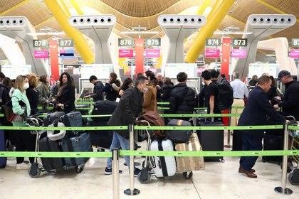 Los pasajeros, con mascarillas protectoras, esperan el check-in antes de abordar sus vuelos a EEUU en el aeropuerto Adolfo Suárez Barajas de Madrid, España el 12 de marzo (Foto: Reuters)