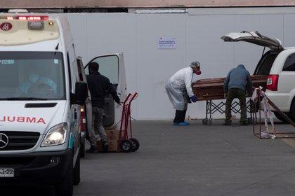 Trabajadores del Hospital San José y operarios funerarios trasladan el cuerpo de un fallecido, este martes en Santiago (Chile). EFE/ Alberto Valdés