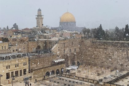 A general view of Jerusalem's Old City shows the Western Wall, Judaism's holiest prayer site, in the foreground and the Dome of the Rock, located on the compound known to Muslims as Noble Sanctuary and to Jews as Temple Mount, in the background, as the snow starts to fall in Jerusalem February 17, 2021 REUTERS/Ilan Rosenberg