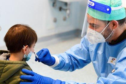 Un médico administra una vacuna contra la gripe a un niño en un hospital militar luego de que las autoridades de salud aconsejaran a las personas que se vacunen contra la gripe para evitar confusión con los síntomas de la enfermedad por coronavirus (COVID-19), en Milán, Italia, el 20 de noviembre de 2020. REUTERS / Flavio Lo Scalzo