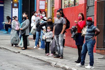 Personas con tapabocas esperan para tomar un bus de transporte público en San Pablo, Brasil (EFE/ Sebastião Moreira)
