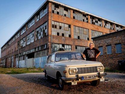Wolfgang Hofmann posa junto a su auto Wartburg, construido en 1974, delante del edificio abandonado de la fábrica VEB de Alemania del Este, donde se construían autos BMW y Wartburg, en el este de Alemania, el 22 de septiembre de 2020. La planta cerró en 1991. (AP Foto/Michael Probst)